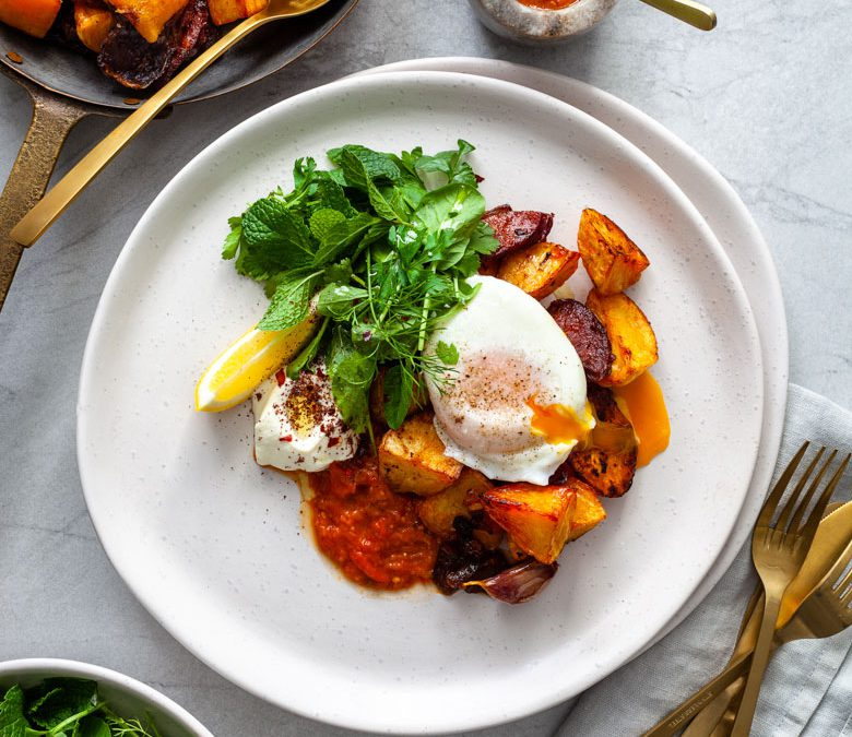 Crispy roast potatoes and chorizo with labne, smoky tomato sauce, herb salad and eggs